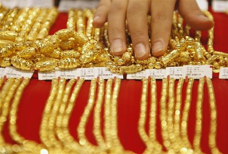 An employee adjusts gold accessories in a glass case at a jewellery shop in Huaibei, Anhui province in this August 5, 2010 file photo. REUTE