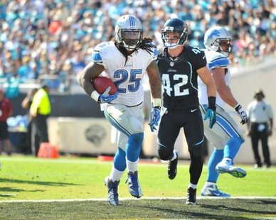 Detroit Lions RB Mikel Leshoure (25) scores one of his three first-half touchdowns as Jacksonville S Chris Prosinski (42) watches during Detroit's 31-13 win at Jacksonville on Nov. 4, 2012 (Photo by Gavin Smith, courtesy of the Detroit Lions)