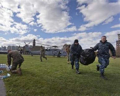 Sailors and Marines arrive in Hoboken, New Jersey with water and supplies from a U.S. Navy Seahawk helicopter for superstorm Sandy relief efforts in this November 3, 2012 handout photo. REUTERS/U.S. Marine Corps/Cpl. Bryan Nygaard