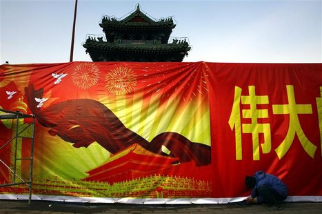 A worker installs a propaganda banner, promoting the Communist Party congress, outside the 700-year-old Dongyue Temple in central Beijing No