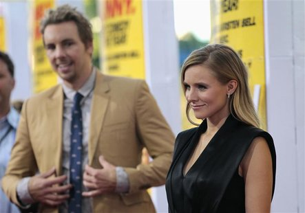"Cast member Kristen Bell poses, as her fiance and co-star Dax Shepard watches, at the premiere of ""Hit and Run"" at Regal Cinemas in Los Ange"
