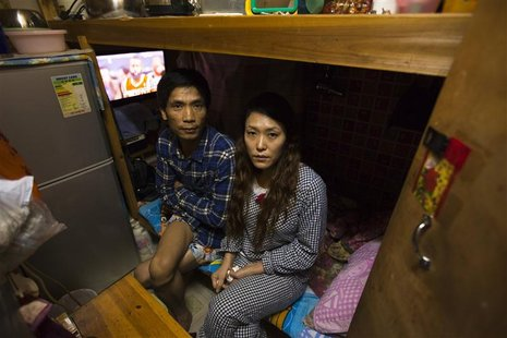 Huang Shaochang, 46, and his wife Li Rong, 37, sit on a bed as they pose for photos in their 35 square feet (3.2 square metres) subdivided f