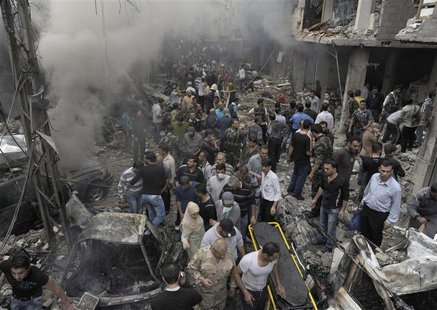A crowd gathers in front of a building and car damaged after a bomb explosion in the Mezzeh 86 area in Damascus, in this handout photograph