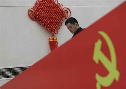 A man walks past a logo of the Communist Party of China (CPC) at a media center for the upcoming18th National Congress of the CPC, which sta