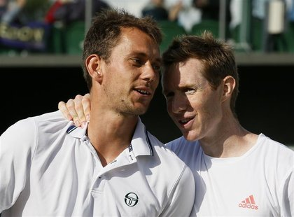 Frederik Nielsen of Denmark (L) and Jonathan Marray of Britain embrace after defeating Bob Bryan of the U.S. and Mike Bryan of the U.S. in t