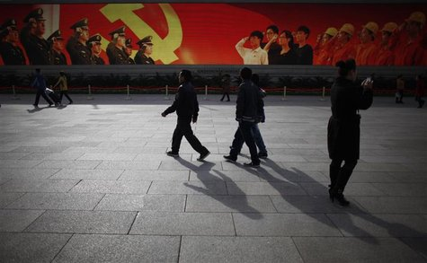 People walk in front of a screen showing propaganda displays near the Great Hall of the People at Beijing's Tiananmen Square, November 7, 20