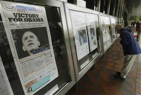 People view various newspaper front pages showing President Barack Obama's victory over Republican presidential candidate Mitt Romney on dis
