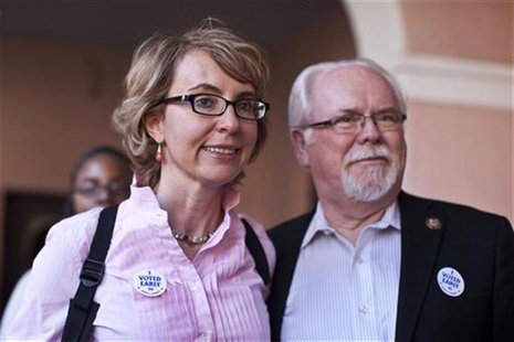Former congresswoman Gabrielle Giffords and Congressman Ron Barber leave the Pima County Recorder's office after casting their ballots in do