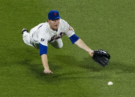 New York Mets left fielder Jason Bay makes a diving attempt to catch a lead-off single by Washington Nationals batter Roger Bernadina in the