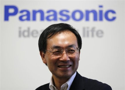 Panasonic Corp's new president Kazuhiro Tsuga poses in front of the company's logo before his interview in Tokyo July 9, 2012. REUTERS/Kim K