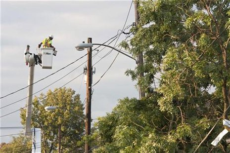A utility worker repairs damage to power lines the morning after the town was hit by a tornado in Elmira, New York July 27, 2012. REUTERS/Ad