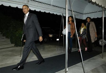 U.S. President Barack Obama, his wife Michelle and their daughters Malia (3rd R) and Sasha (2nd R) return after his re-election, to the Whit