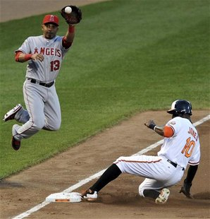 Los Angeles Angels third baseman Maicer Izturis (L) fails to make the out as Baltimore Orioles base runner Adam Jones steals in the fourth i