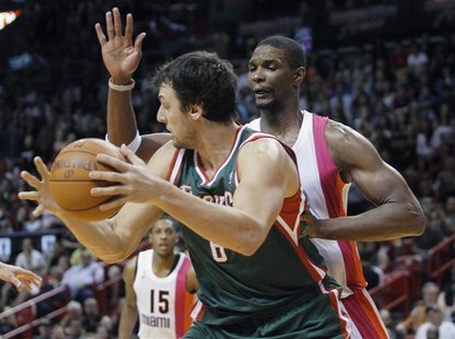 The Miami Heats' Chris Bosh (R) defends against Milwaukee Bucks' Andrew Bogut during their NBA basketball game in Miami, Florida January 22,