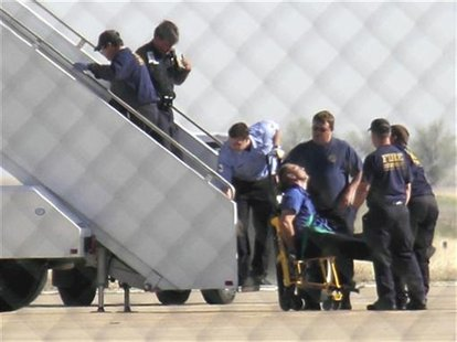 JetBlue pilot captain Clayton Osbon, is removed from the plane after erratic behavior forced the crew to land in Amarillo, Texas, in this fi