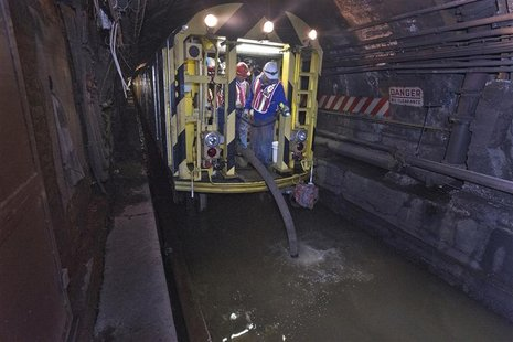 MTA employees use a pump train and work around the clock to remove seawater out of the L train's tunnel under the East River in the aftermat