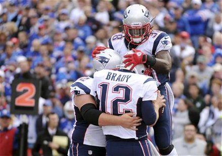 New England Patriots offensive lineman Ryan Wendell (L), quarterback Tom Brady (12) and running back Brandon Bolden (38) celebrate Brady's r