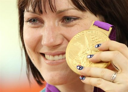 Australia's Anna Meares holds up her gold medal after the track cycling women's sprint finals at the Velodrome during the London 2012 Olympi