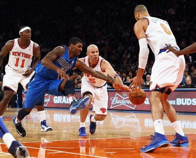 Dallas Mavericks guard O.J. Mayo (2nd L) and New York Knicks point guard Jason Kidd (C) fight for a loose ball in front of Knicks center Tys