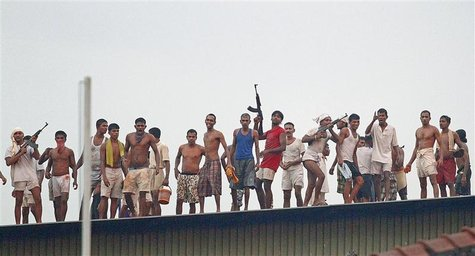 Rioting prisoners from Welikada prison fire weapons from the roof during a clash between Sri Lanka's Special Task Force (STF) at Welikada pr