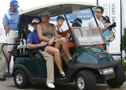 Rory McIlroy of Northern Ireland and girlfriend tennis player Caroline Wozniacki of Denmark ride in a buggy after the rain-delayed second ro