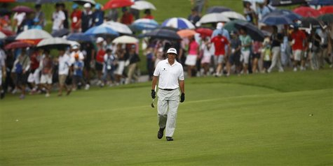 Phil Mickelson of the U.S. walks down the eighth fairway as spectators carrying umbrellas follow in the light drizzle during the rain-delaye
