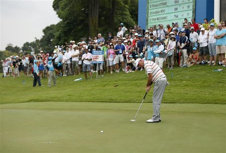 Thomas Bjorn of Denmark putts on the ninth hole during the rain-delayed second round of the Barclays Singapore Open golf tournament in Sento