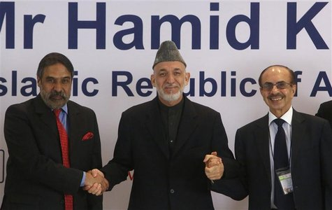 Afghanistan's President Hamid Karzai (C) shakes hands with India's Trade Minister Anand Sharma (L) and Chairman of the Godrej Group Adi Godr