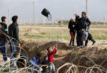 Syrians throw their belongings while trying to cross a ditch after crossing from the northern Syrian town of Ras al-Ain to Turkey in the bor