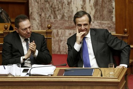 Greece's Finance Minister Yannis Stournaras (L) applauds as Prime Minister Antonis Samaras looks on during a parliament session in Athens No