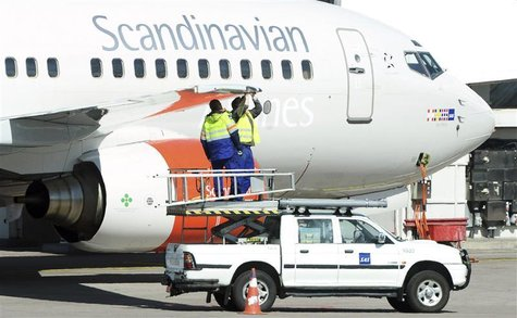 Technicians work on the wing of a Scandinavian airline SAS Boeing 737 aircraft at the Stockholm-Arlanda airport in Sweden May 3, 2012. REUTE