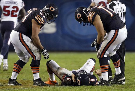 Chicago Bears quarterback Jay Cutler (6) lies on the field after being hit late on a play by the Houston Texans with his teammates over him