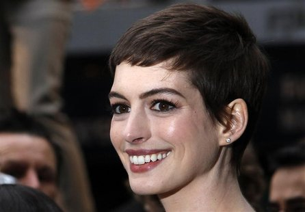 "Actress Anne Hathaway poses for photographers as she arrives at the European Premiere of ""The Dark Knight Rises"" in Leicester Square, centra"