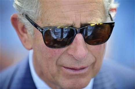 An emergency services member is reflected in the sunglasses of Britain's Prince Charles during a reception at Bondi Icebergs swimming club i