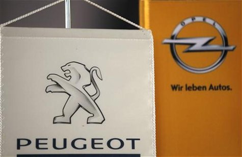 The logo of German General Motors daughter Opel and French car maker Peugeot are seen at a Opel and Peugeot dealership in Leverkusen near Co