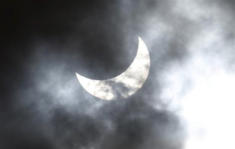 Clouds obscure the moon passing in front of the sun as it approaches a full solar eclipse in the northern Australian city of Cairns November