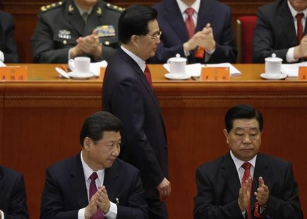 China's Vice President Xi Jinping and top political advisor Jia Qinglin applaud as China's President Hu Jintao walks past after delivering s