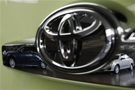 Toyota's Corolla Fielder (L) and Corolla Axio are reflected in a Toyota Forte's logo at the company's headquarters in Tokyo November 5, 2012