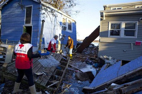 Red Cross volunteers Jessica Elam and Gilbert Abney check on Rob Fragetti, who is attempting to salvage items with his neighbors in their de