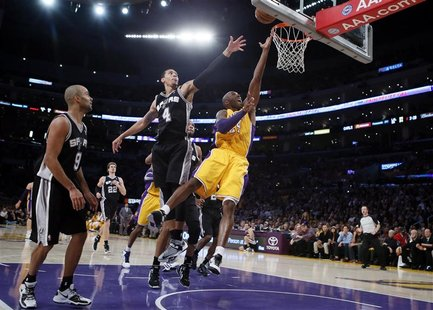 Los Angeles Lakers Kobe Bryant (R) goes up to shoot against the San Antonio Spurs during their NBA basketball game in Los Angeles, November
