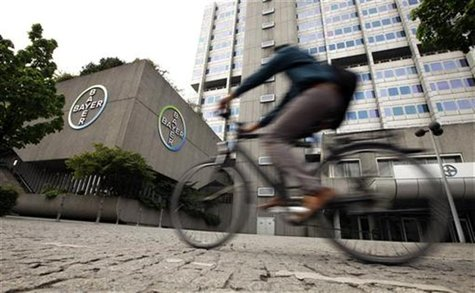 A man rides a bicycle in front of the building of Germany's largest drugmaker Bayer HealthCare Pharmaceuticals in Berlin April 28, 2011. REU