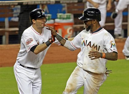 Miami Marlins shortstop Jose Reyes (R) celebrates with teammate Gil Velazquez after Reyes scored the winning run over the New York Mets on a