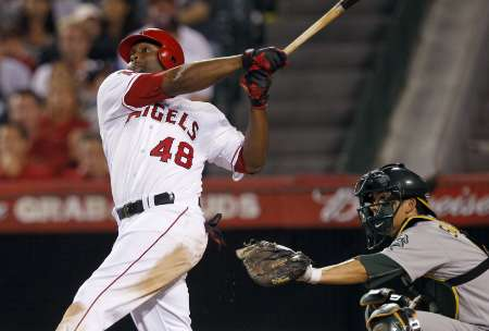 Los Angeles Angels' Torii Hunter (L) follows through hitting a two-run home run against the Oakland Athletics during the sixth inning of their MLB American League baseball game in Anaheim, California September 24, 2011. Oakland Athletics catcher Kurt Suzuki (R) looks on from behind the plate. REUTERS/Alex Gallardo (UNITED STATES - Tags: SPORT BASEBALL)