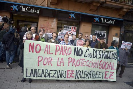 "Protesters hold a banner reading ""No to Unemployment. No to Evictions. For Social Protection"" during a demonstration in front of the Caixa B"