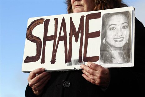 Mary Phelan holds a picture of Savita Halappanavar in protest outside University Hospital Galway in Galway, Ireland November 15, 2012. The I