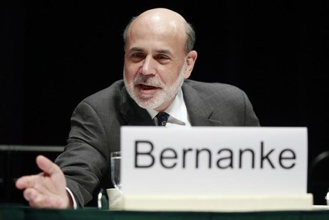 Federal Reserve Chairman Ben Bernanke leans forward to speak with someone before addressing the Economic Club of Indiana in Indianapolis Oct