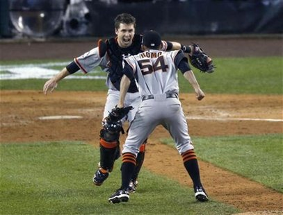 San Francisco Giants relief pitcher Sergio Romo (R) jumps into the arms of catcher Buster Posey (L) after defeating the Detroit Tigers to wi