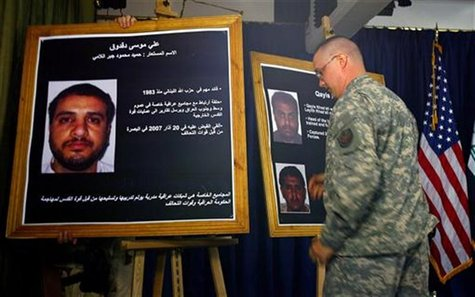 A U.S. solider shows a picture of Ali Mussa Daqduq (L) during a news conference at the heavily fortified Green Zone area in Baghdad July 2,