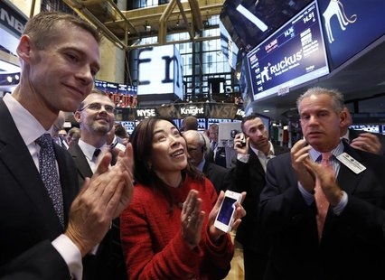 Selina Lo (C), President and CEO of of Ruckus Wireless, applauds as her company's stock begins trading on the floor of the New York Stock Ex