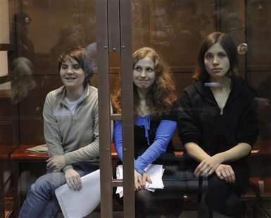 "Members of the female punk band ""Pussy Riot"" (L-R) Yekaterina Samutsevich, Maria Alyokhina and Nadezhda Tolokonnikova sit in a glass-walled"